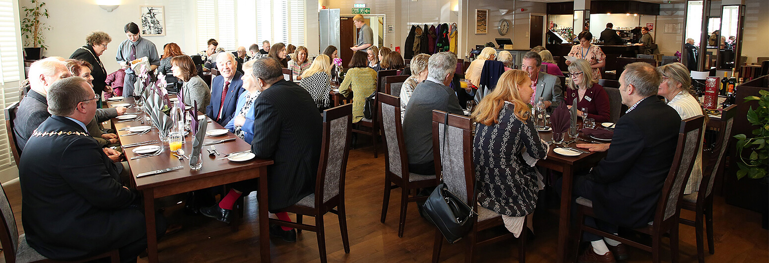 Busy restaurant with patrons wearing suits and dresses